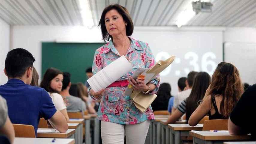 na profesora reparte los exámenes a los estudiantes del primer examen de las Pruebas de Acceso a la Universidad-