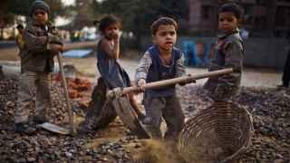 Niños en la India trabajan cerca de sus padres en unas obras de construcción en 2010.