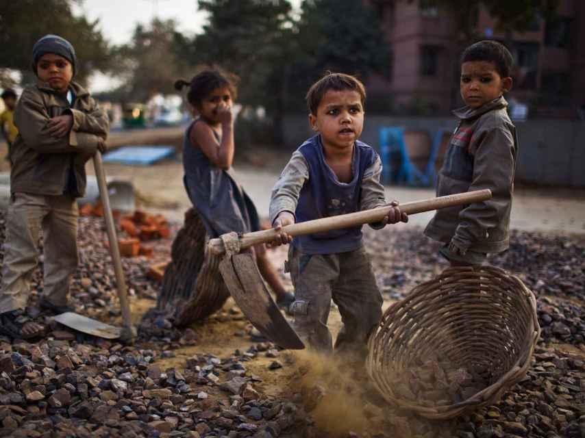 Niños en la India trabajan cerca de sus padres en unas obras en 2010.