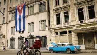 Un hombre pasea en bicicleta por una calle de La Habana.