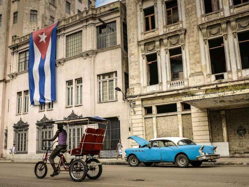Un hombre conduciendo un bicitaxi en una calle de La Habana.