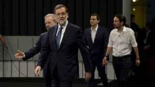 Mariano Rajoy en primer plano, con Iglesias y Rivera al fondo.