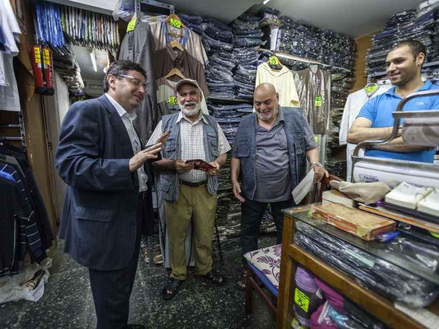 El número seis del PSC al Congreso conversando con otros musulmanes en una tienda de ropa.