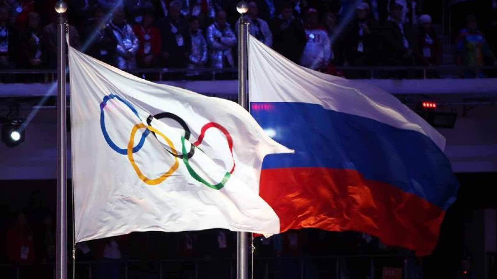 La bandera rusa al lado de la de los Juegos Olímpicos.