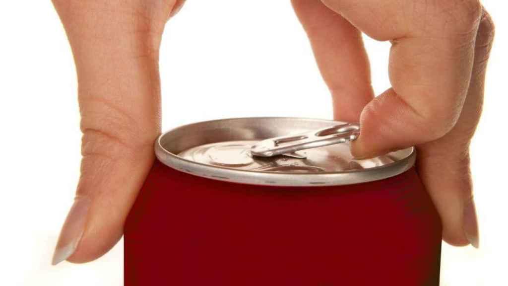 Una mujer a punto de abrir un refresco.
