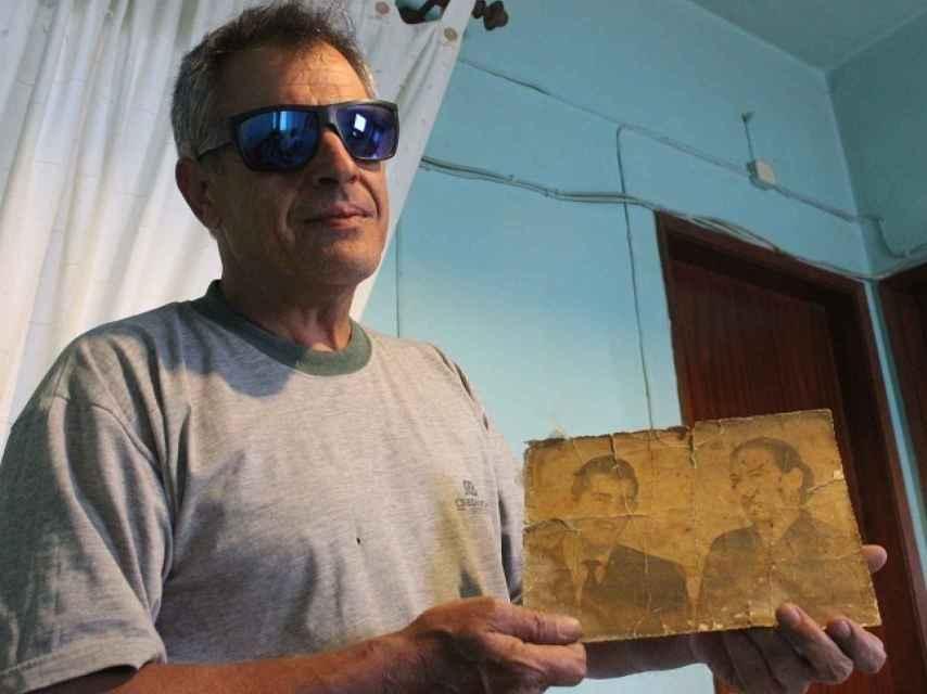 Lino, nieto de Aurora, muestra una foto de su padre y su abuela