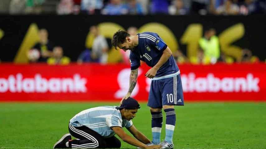 Un aficionado le besa las botas a Messi.
