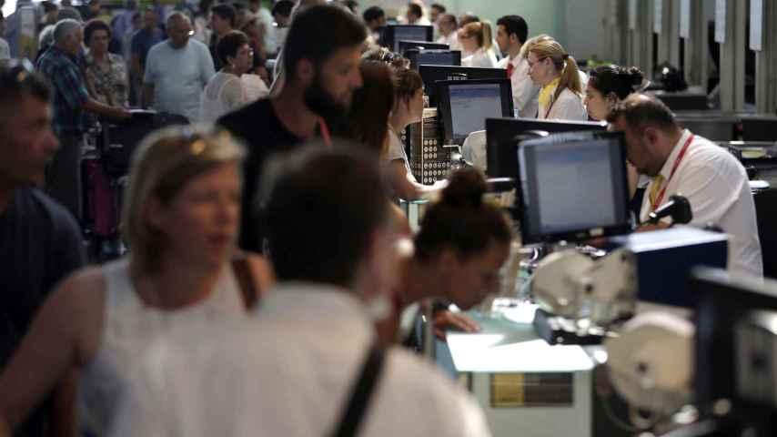 Personal de facturación de Vueling atiende a los viajeros en el Aeropuerto de El Prat