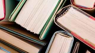 Varios libros amontonados en una estantería.