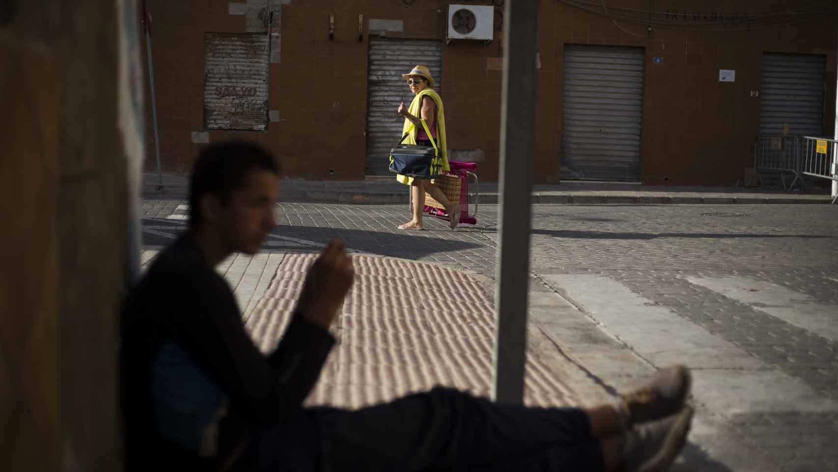Sofyan, sentado en una esquina mientras un vecino vuelve de la playa.