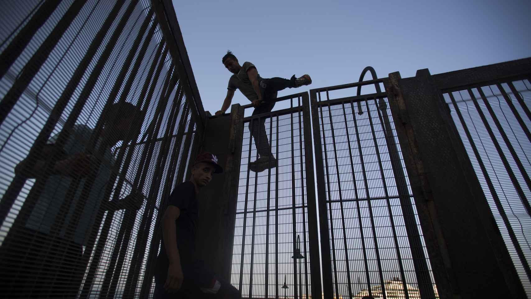 En el centro, Mohamed, junto a dos menores que saltan la valla del puerto melillense.