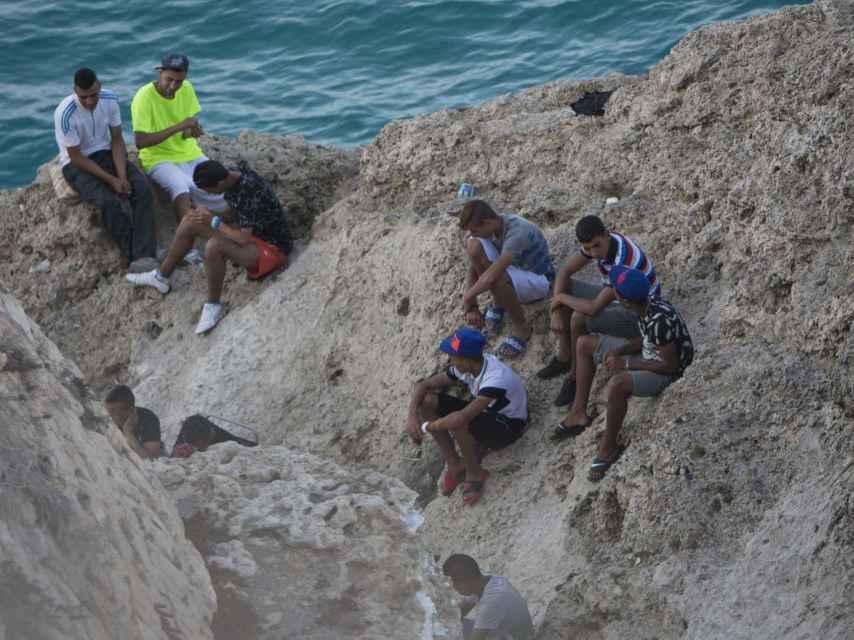 Grupo de menores en las escolleras del puerto melillense, donde viven en la indigencia.