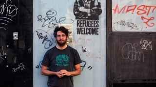 Noaz junto a su plantilla de Juncker, en Alonso Martínez, tras quitarle las pegatinas nazis que habían colocado para tapar las letras de 'Refugees welcome'.