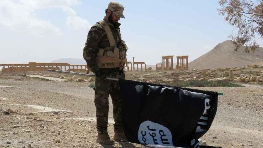 Un soldado sirio retira una bandera del Estado Islámico en Siria.