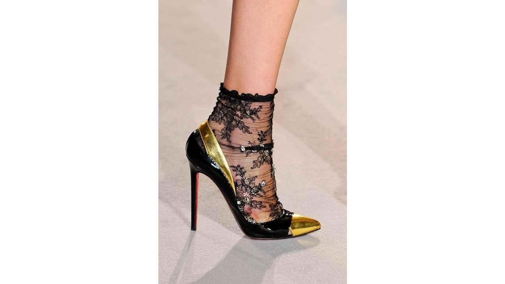 Tacones de charol negros y dorados de Christian Louboutin combinados con medias cortas de encaje.