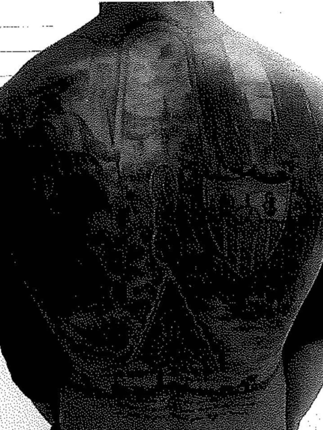 Tatuaje del escudo del Sevilla que el militar lleva en la espalda.