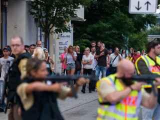Un grupo de ciudadanos espera en las afueras del centro comercial Olympia durante el tiroteo.