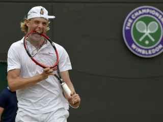 Denis Shapovalov muerde la raqueta durante un partido de Wimbledon.