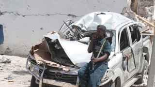 Un policía apoyado en un coche destruido tras la explosión.