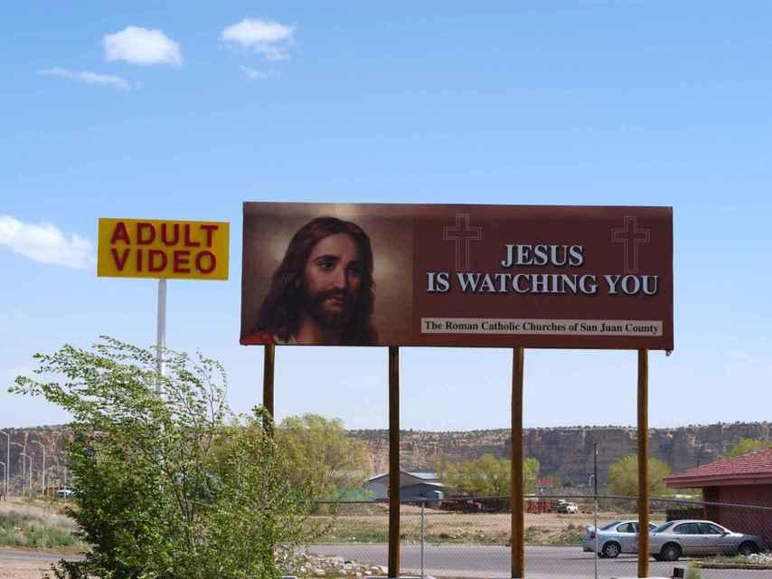 Un cartel de una iglesia junto a un anuncio de un sex shop.
