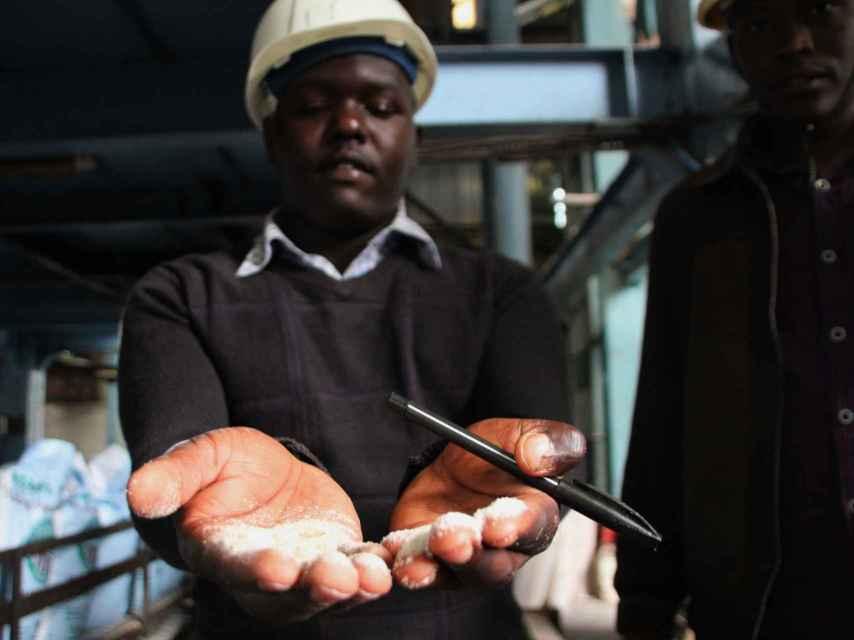 Un representante de Transmara Sugar Company sostiene un puñado de azúcar.