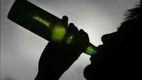 Un hombre bebe una cerveza al atardecer.