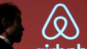Un hombre pasa por delante del logo de Airbnb.