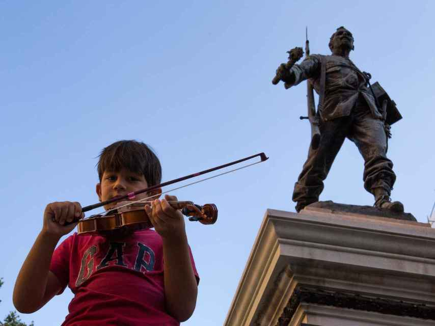 Un joven violinista junto a la estatua de Eloy Gonzalo, en la Plaza de Cascorro, epicentro de las fiestas de San Cayetano.