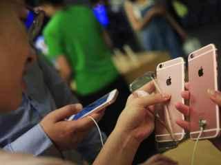 Un joven compara dos iPhone en una tienda.
