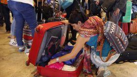Una mujer abre su maleta en el aeropuerto.
