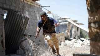 Un soldado libio intenta cubrirse en la batalla por Sirte.