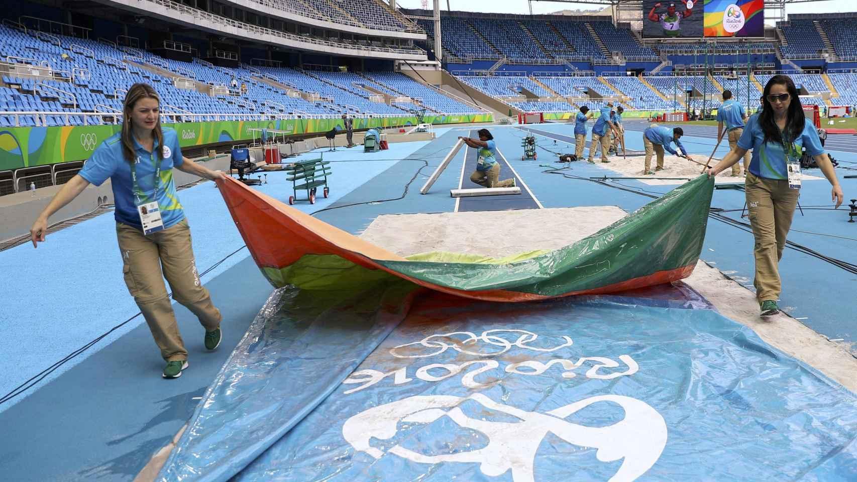 Unos voluntarios realizan los últimos preparativos en la pista de atletismo de Enghenao.