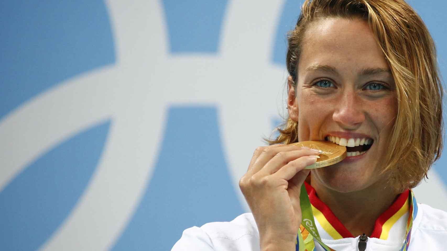 La nadadora española muerde su oro, el primero de la natación española desde Barcelona'92.