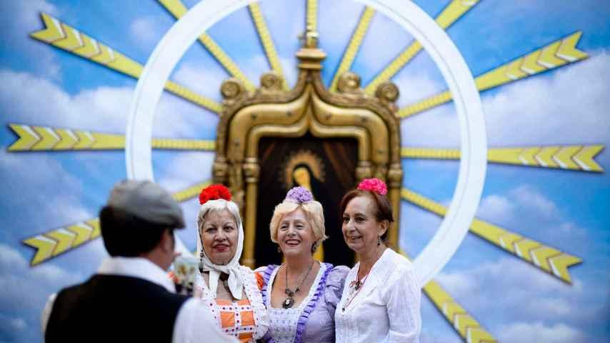 Manolas, mujeres vestidas con el traje tradicional, con la Virgen de la Paloma de fondo.