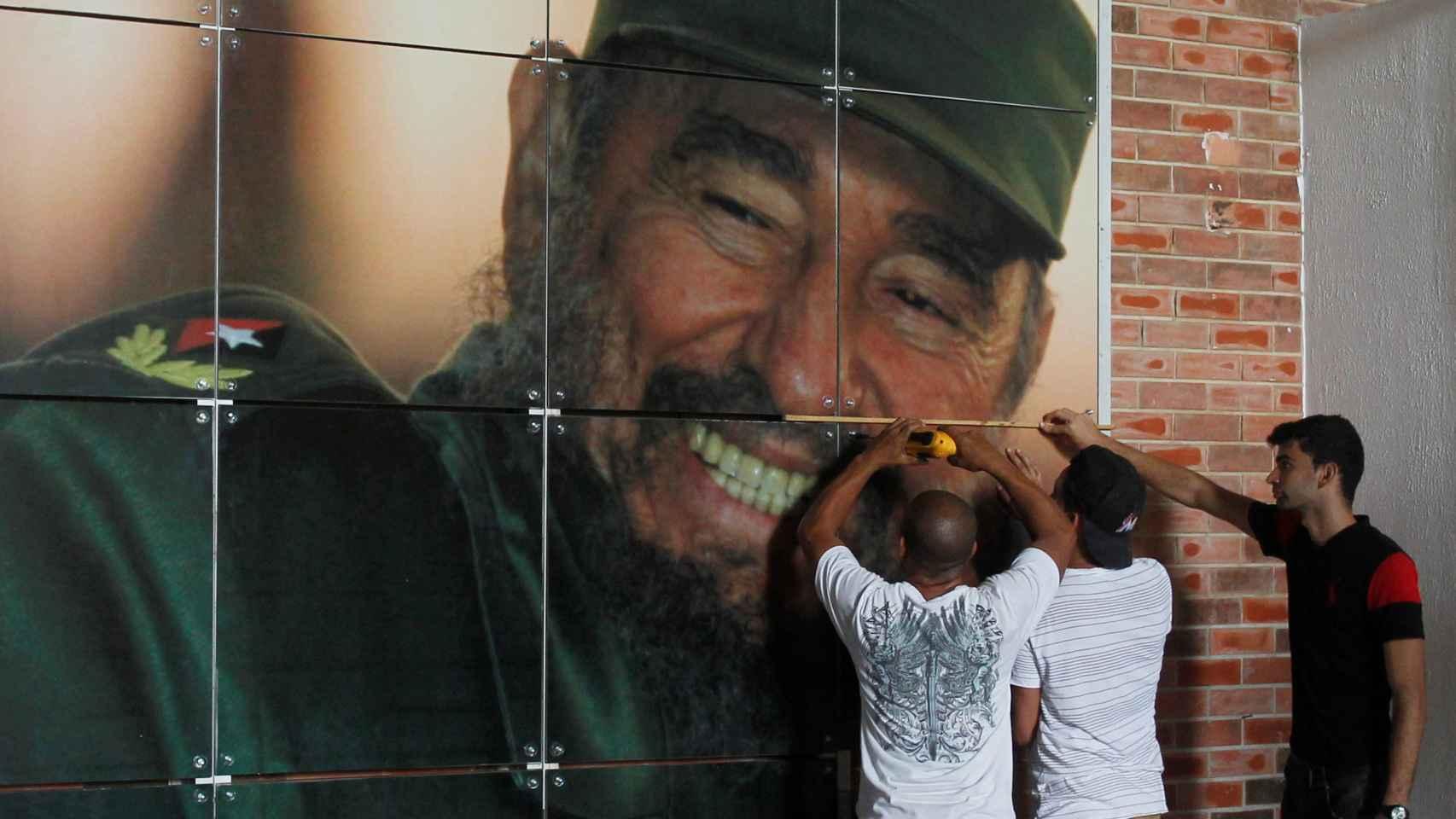Unos trabajadores instalan un mural del expresidente cubano para la exposición por su 90 cumpleaños.
