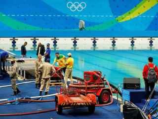 Operarios de Río cambian el agua de la piscina.