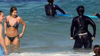 Una mujer con un burkini en una playa.