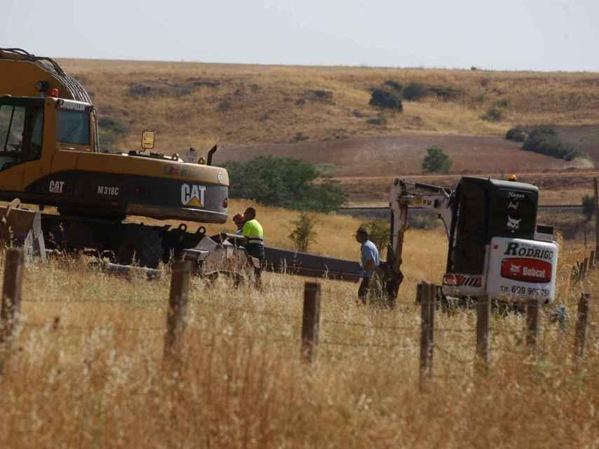 Varios efectivos de búsqueda trasladan el cadáver del pastor.