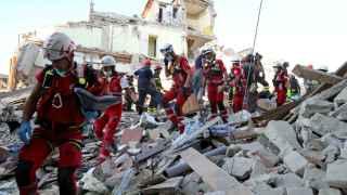 Los equipos de rescate caminan sobre los escombros buscando supervivientes.