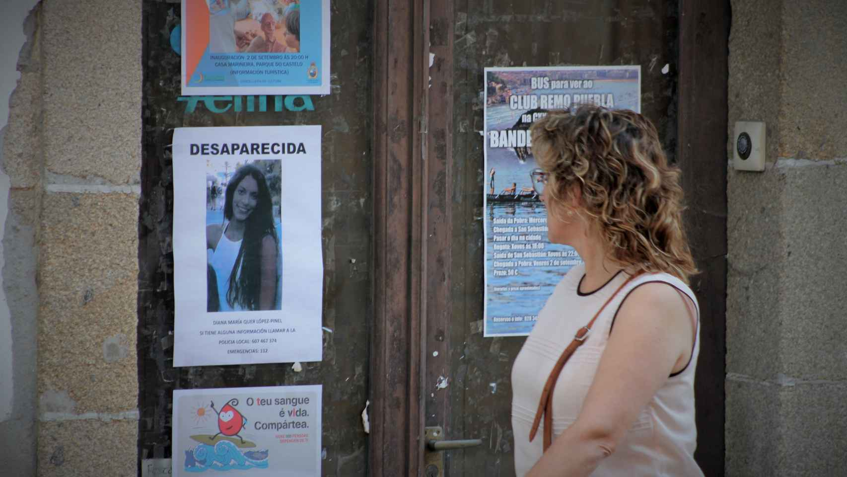 Una mujer pasa junto a un cartel con sobre Diana Quer en A Pobra.