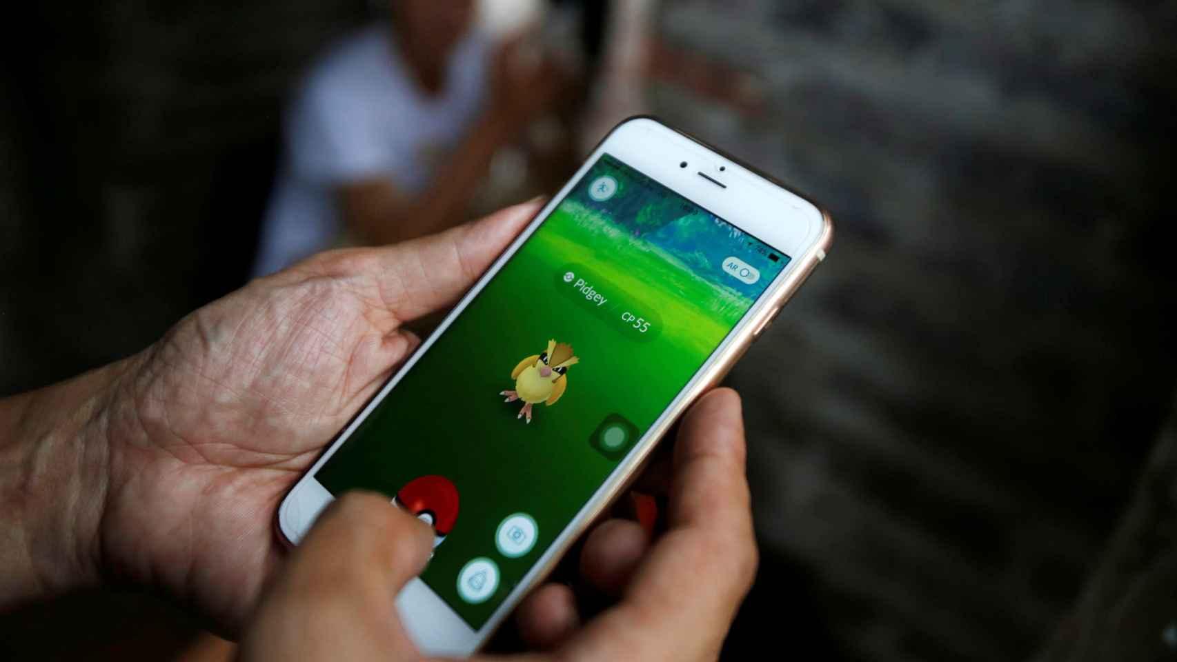 Un hombre jugando a Pokemon Go en su móvil.