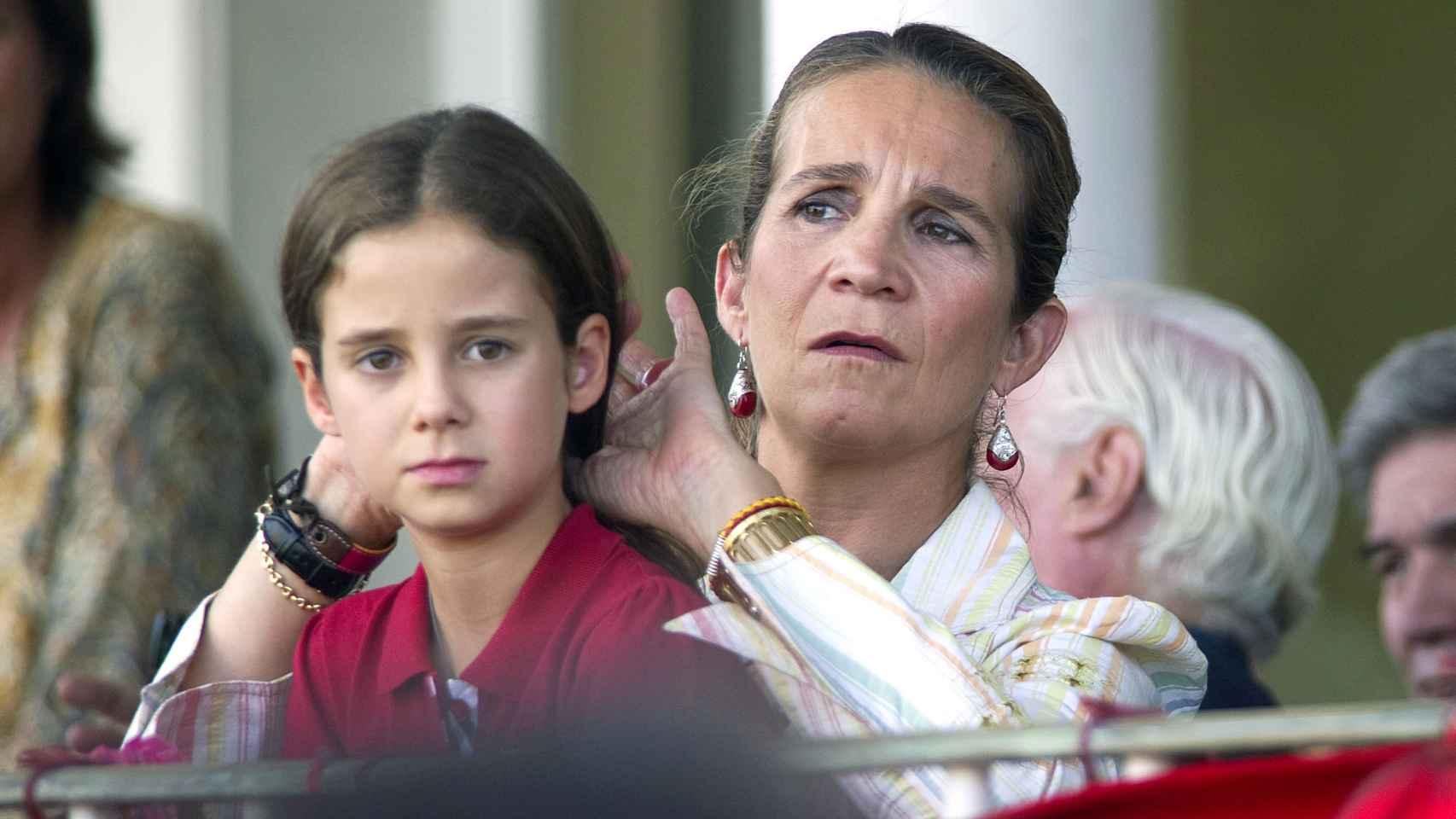 La infanta Elena recoge cariñosamente la melena de su hija.