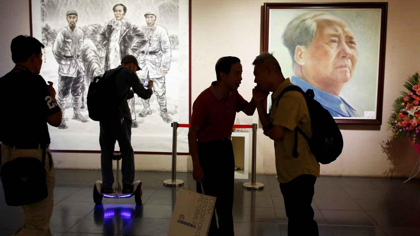 Visitantes ante ilustraciones de Mao Zedong en una exhibición en Pekín. REUTERS/Thomas Peter