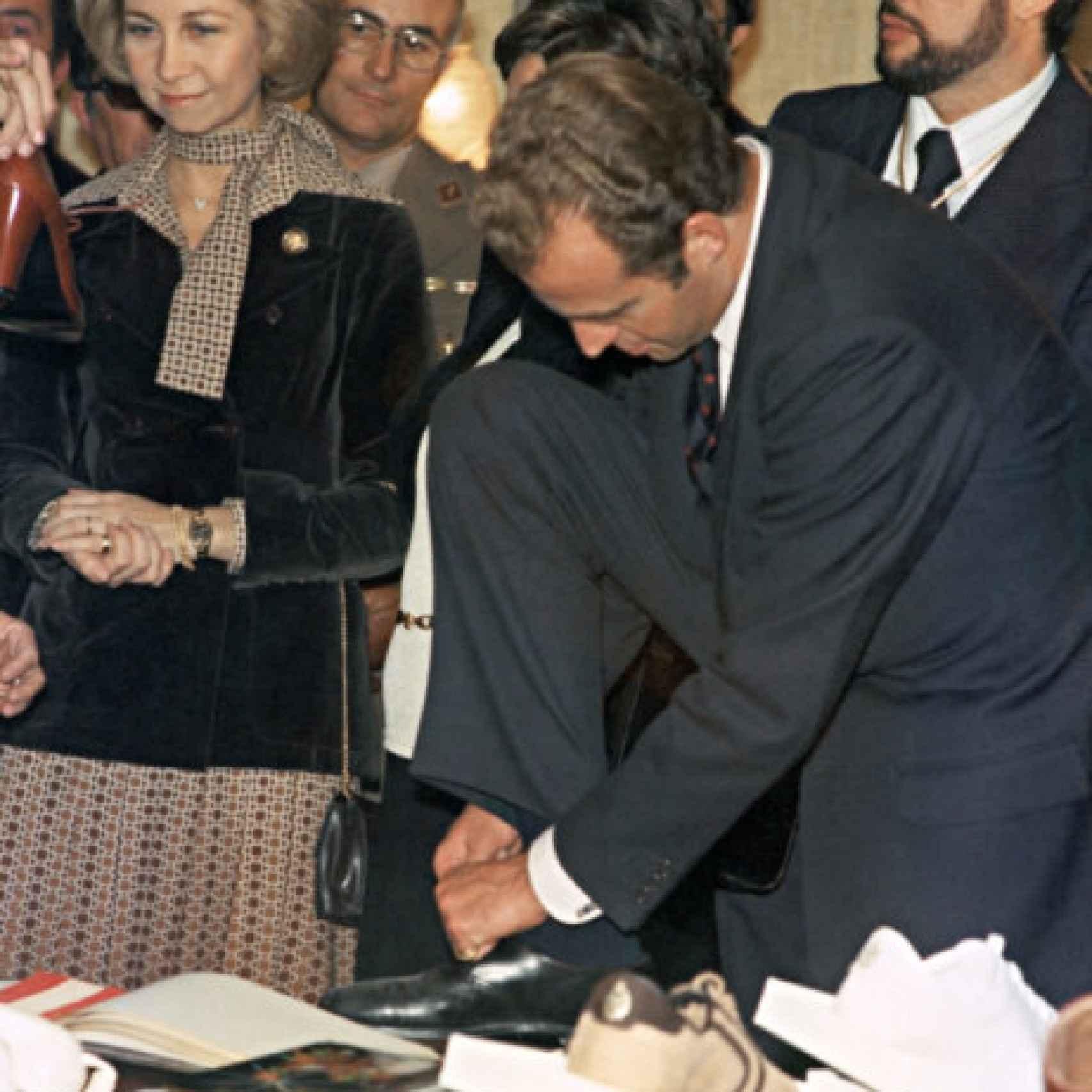 El rey emérito atándose los zapatos junto a la reina Sofía