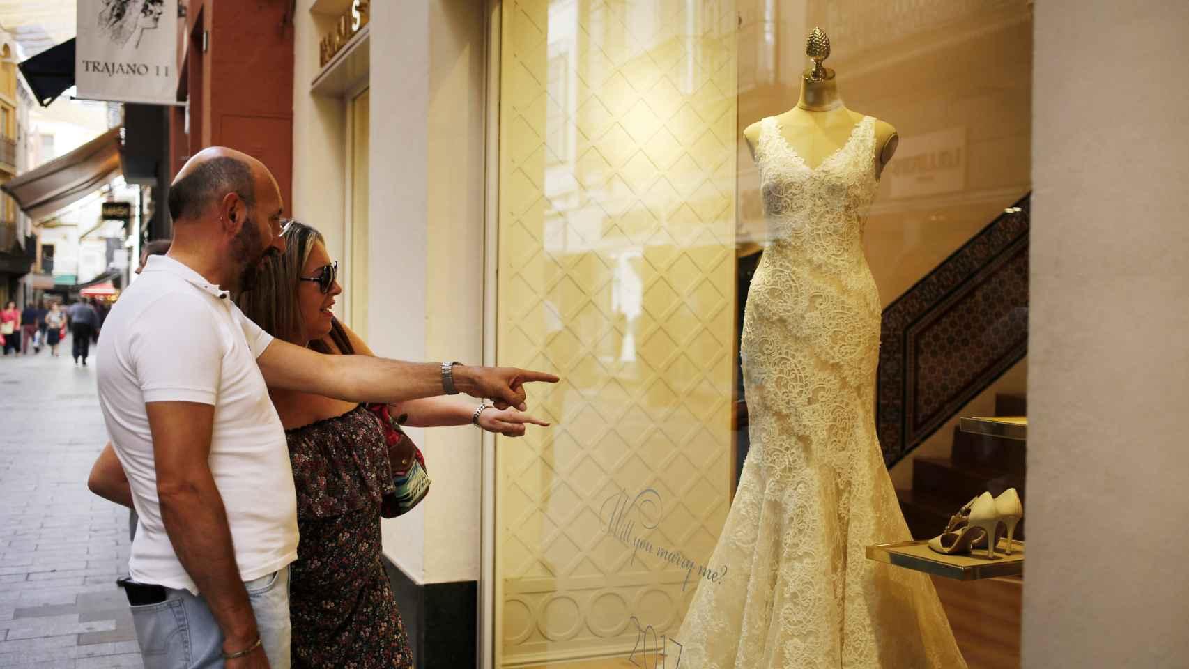 La pareja viendo un vestido de novia un escaparate