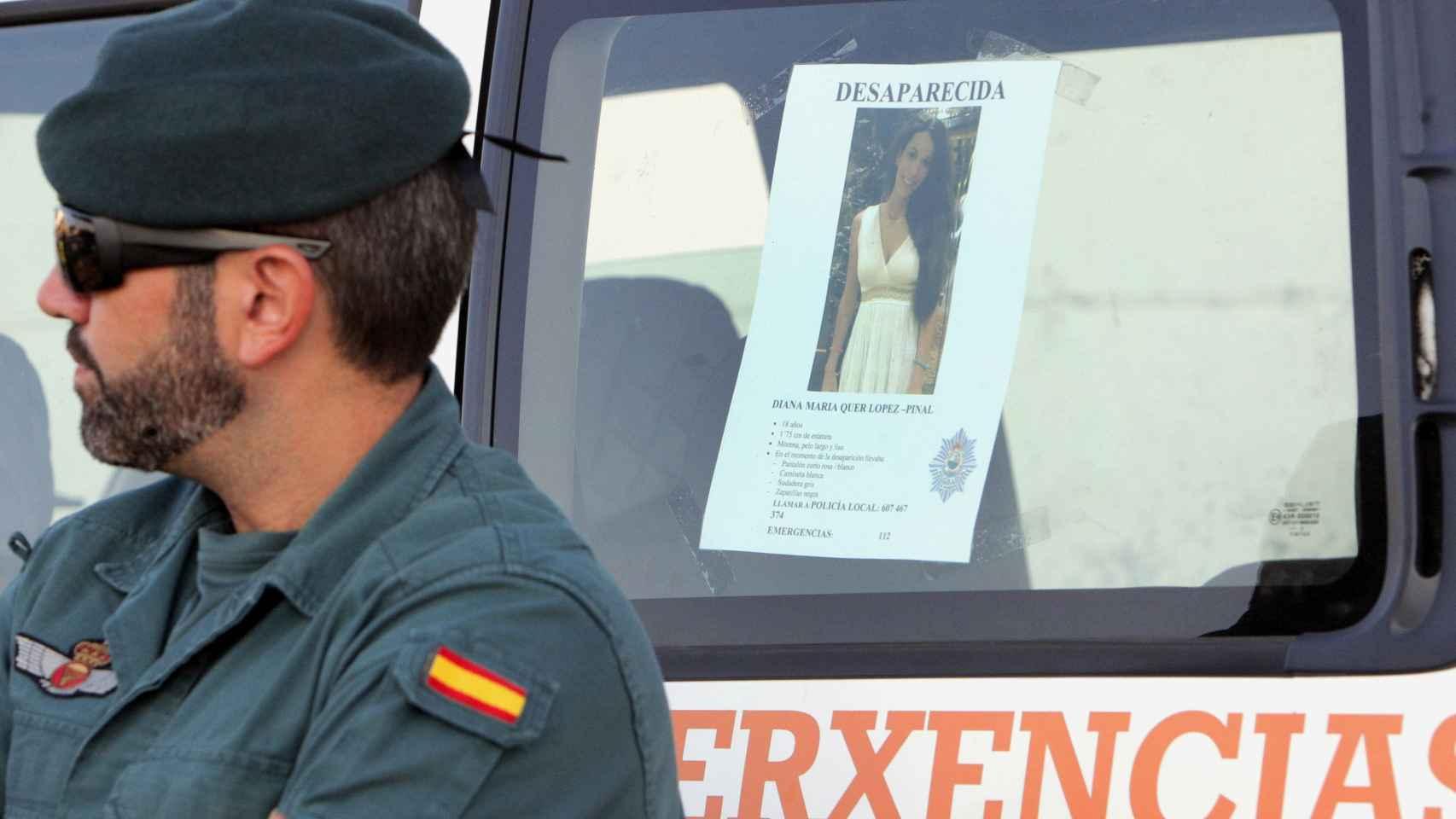 Un efectivo de la Guardia Civil junto a la imagen de Diana Quer