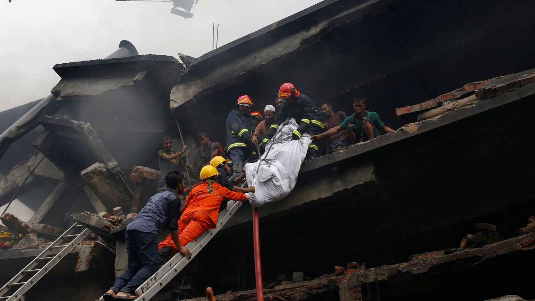 Los bomberos rescatan uno de los cadáveres