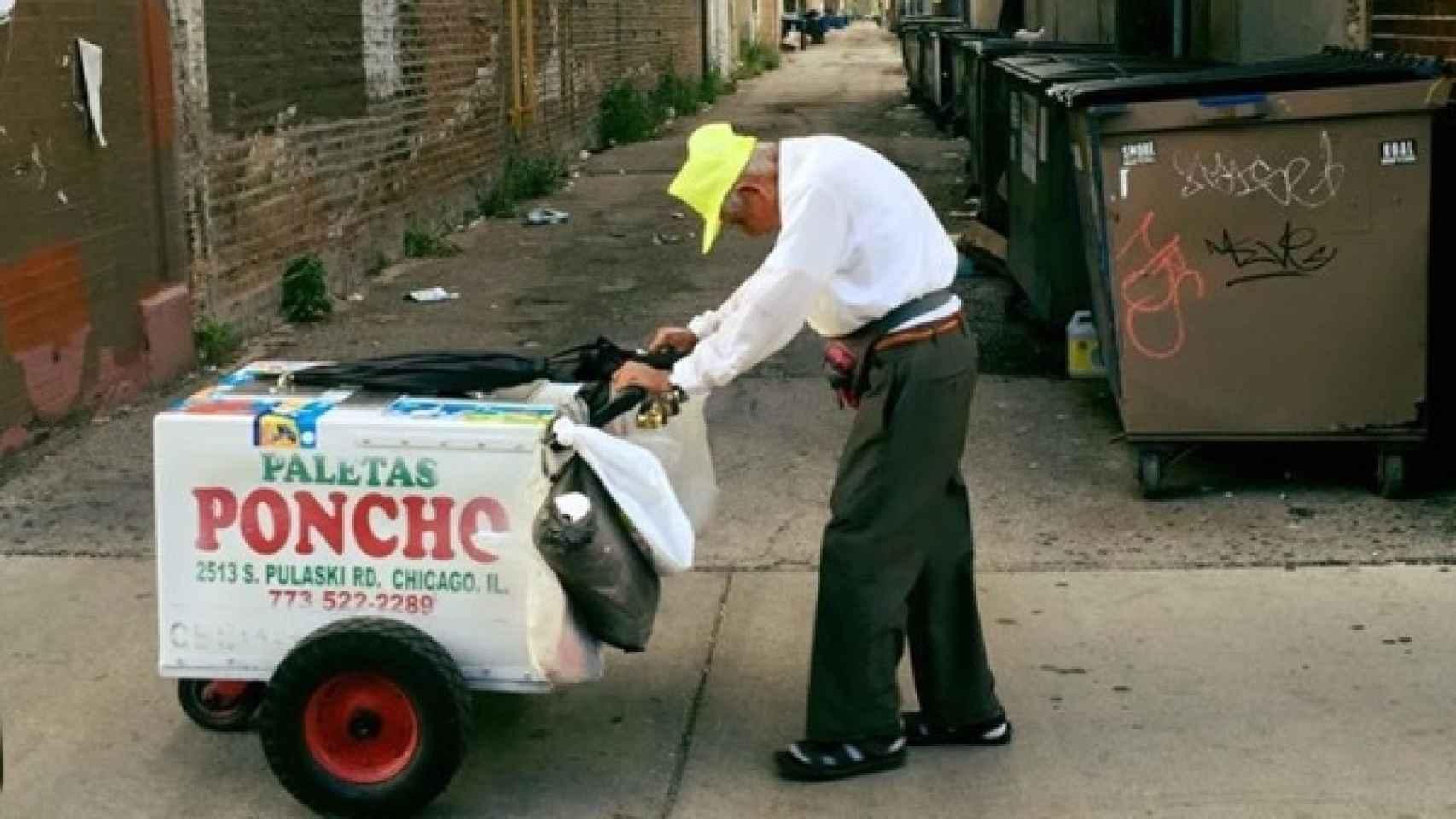 Fidencio arrastrando su carrito de helados con su característica gorra amarilla.