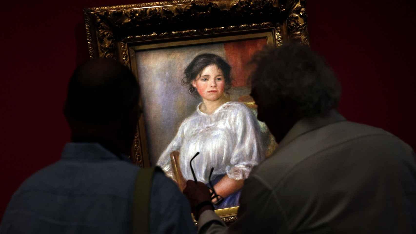 Dos hombres observan la obra Jeune fille assise (1909), de Auguste Renoir.
