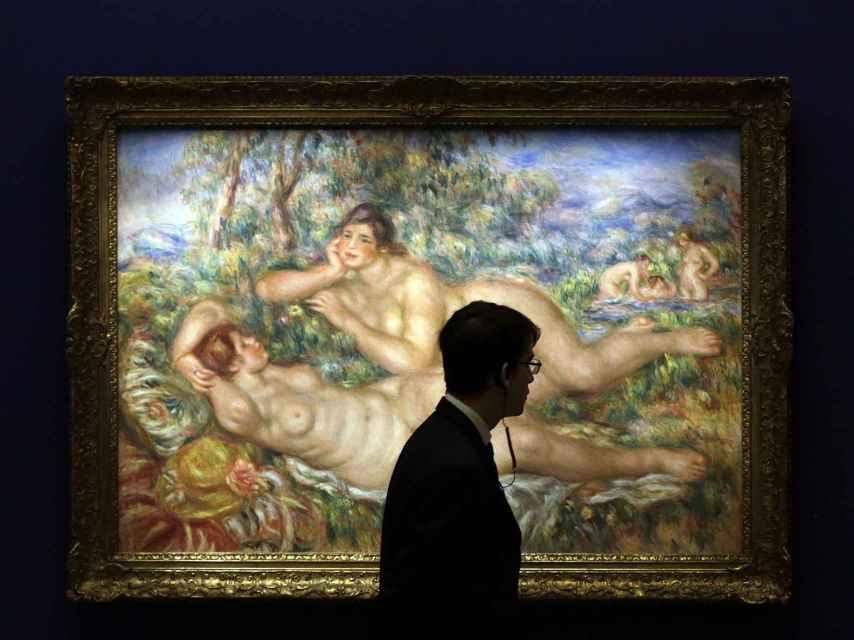Un vigilante pasa ante la obra Les baigneuses (1919), de Auguste Renoir, que se muestra en la exposición.